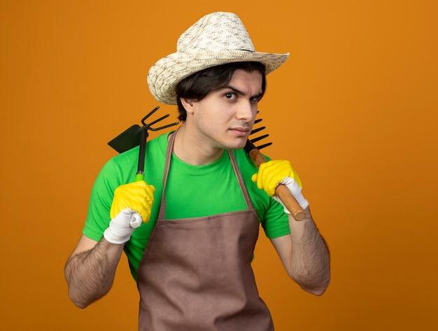 Sospettoso giovane giardiniere maschio in uniforme che indossa cappello da giardinaggio con guanti tenendo la zappa rastrello con rastrello sulla spalla isolato su arancione