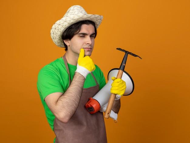 Sospettoso giovane giardiniere maschio in uniforme che indossa cappello da giardinaggio con guanti che tengono altoparlante con il mento afferrato rastrello