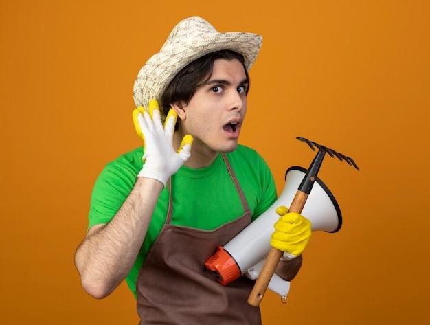 Sospettoso giovane giardiniere maschio in uniforme che indossa cappello da giardinaggio con guanti tenendo l'altoparlante con rastrello che mostra ascolta gesto isolato su arancione