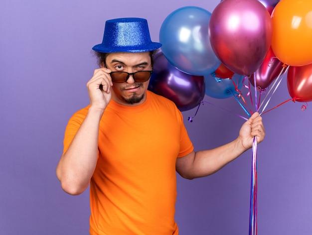 Giovane sospettoso che indossa un cappello da festa con gli occhiali che tengono palloncini isolati sul muro viola