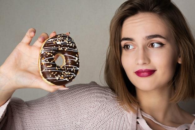 灰色の背景にドーナツを保持している不審な若いモデル。テキスト用のスペース