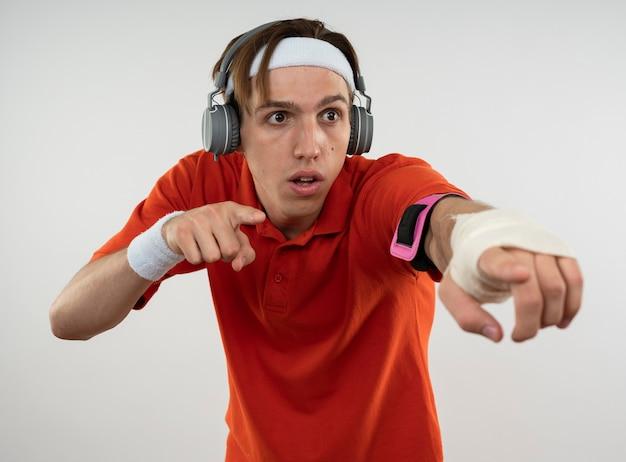Подозрительный молодой спортивный парень с повязкой на голову с браслетом и наушниками с повязкой на руке телефона указывает на сторону, изолированную на белой стене