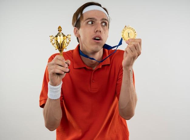 Sospettoso giovane ragazzo sportivo che indossa la fascia con il braccialetto che tiene la tazza del vincitore con la medaglia isolata sulla parete bianca