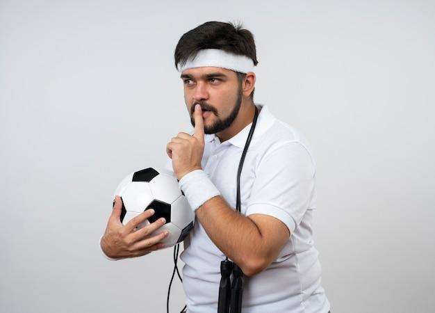 Подозрительный молодой спортивный мужчина смотрит в сторону, носит повязку на голову и браслет со скакалкой на плече, держа мяч, показывая жест тишины, изолированный на белой стене