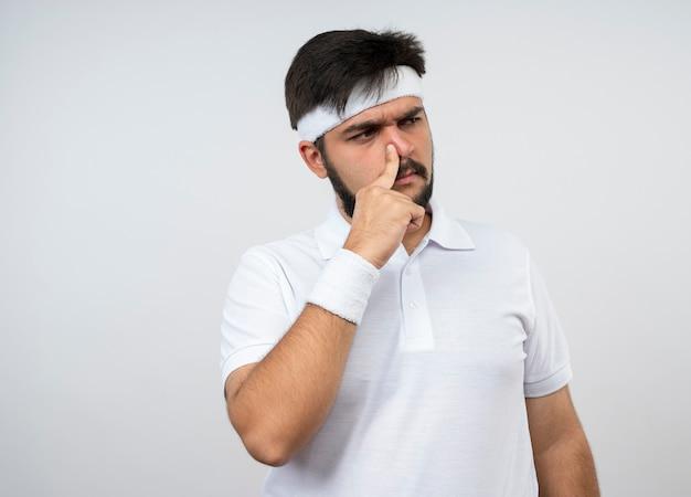 Sospettoso giovane uomo sportivo guardando al lato che indossa la fascia e il braccialetto mettendo il dito sul naso isolato sul muro bianco