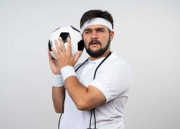 Sospettoso giovane uomo sportivo che indossa la fascia e il braccialetto con la corda per saltare sulla spalla tenendo palla intorno al viso isolato sul muro bianco