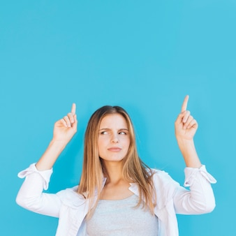 Suspicious young woman pointing her finger upward against blue background