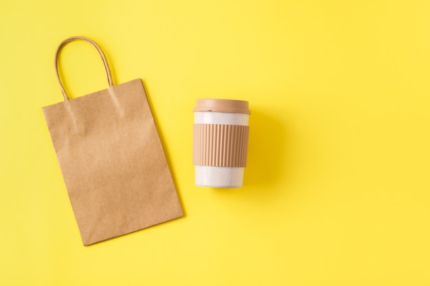 Sustainable bamboo reusable cofee cup for travel to go and paper kraft bag. takeaway mug with spill