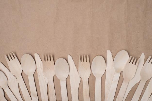 持続可能なカトラリーのコンセプト。クラフト紙の背景テーブルに分離された木製のカトラリーの列の俯瞰写真の上の上