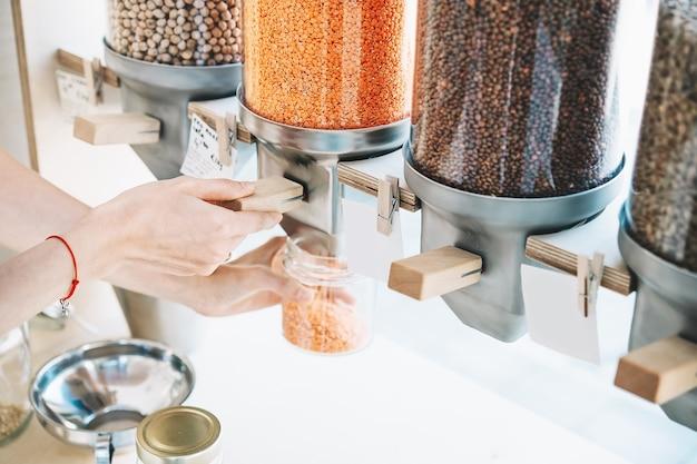 地元の小さな企業での持続可能な買い物女性はディスペンサーからガラスの瓶に赤レンズ豆を注ぐ
