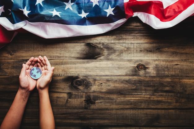 持続的な地球の概念木製の背景と米国旗に惑星地球を保持している人間の手