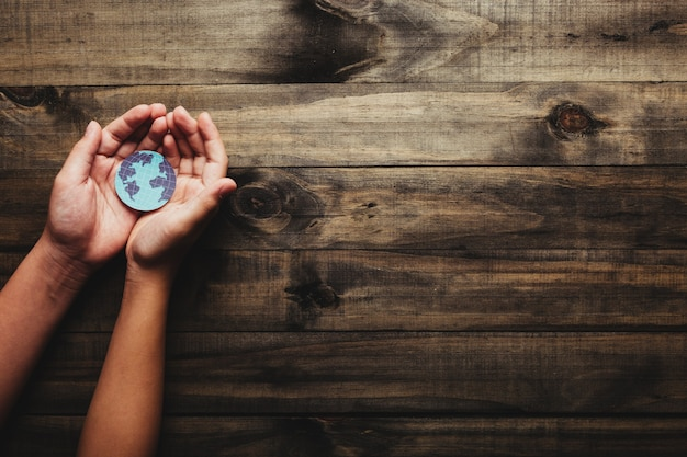 Sustained earth concept: human hands holding the planet earth on the wooden background.
