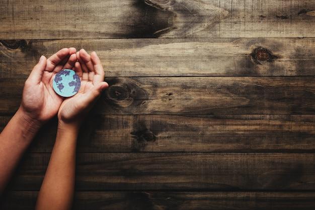 持続的な地球の概念:木製の背景に惑星の地球を保持している人間の手。