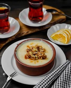 Sutlach, dessert nazionale con noci e un bicchiere di tè.
