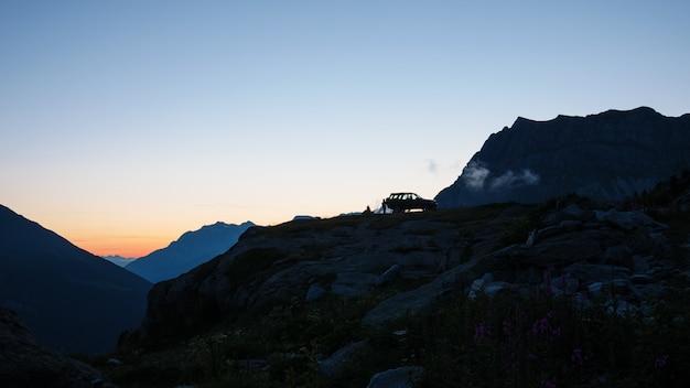 山頂のsuv 4x4車、日没時の風光明媚な風景、アルプスの冒険探検の放浪癖。