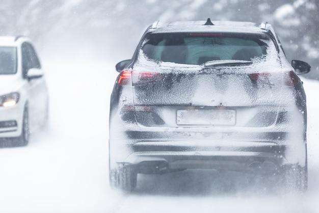 雪のせいで登録番号が見えない、森の中の雪に覆われた滑りやすい道路を走るsuv車。