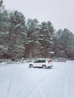 눈 덮인 숲 복사 공간 한가운데에 있는 suv 자동차