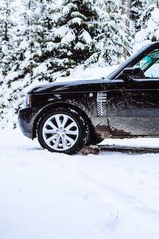 Suv car in snowed forest copy space