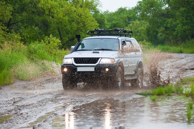 많은 물이 튀는 빗속에서 물 위를 달리는 suv
