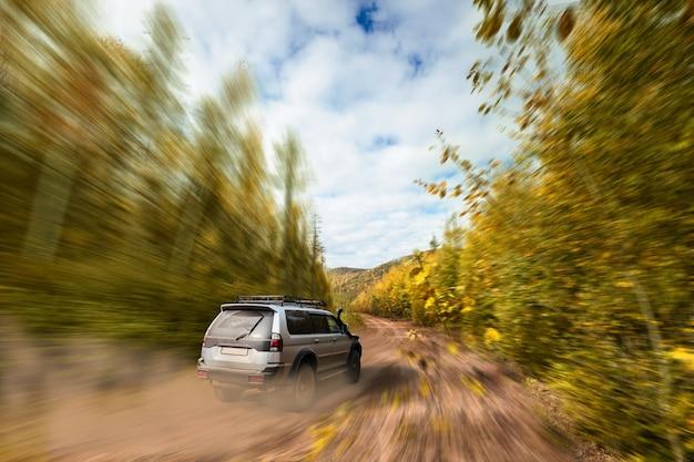 숲 속 비포장도로에서 빠르게 움직이는 suv
