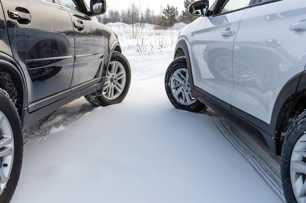雪原に駐車している白と黒のsuv車。