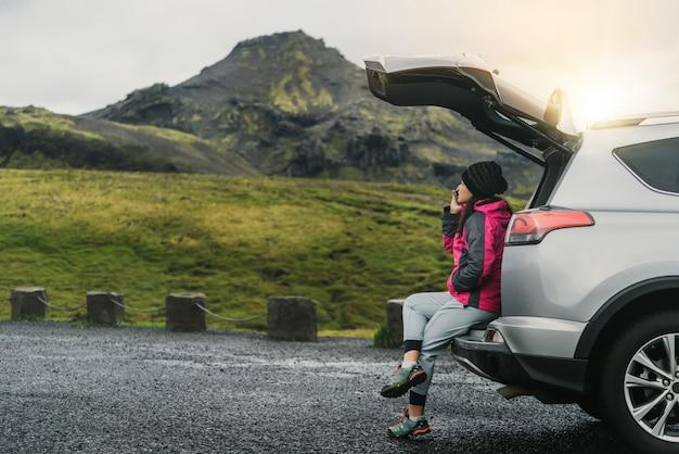 女性観光客がアイスランドでsuv車で旅行します。