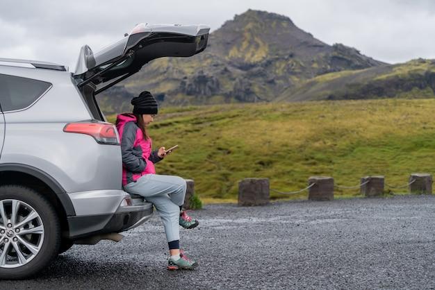 アイスランドのsuv車で女性観光客が旅行します。