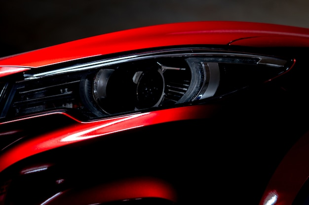 Фара крупного плана сияющего красного автомобиля компакта suv роскоши. технология элегантных электромобилей