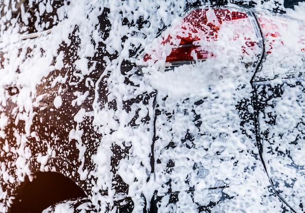 スポーツとモダンなデザインの黒いコンパクトsuv車の背面図は、水と白い泡で洗っています。
