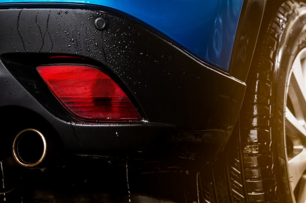 スポーツデザインの青いコンパクトsuv車は水で洗っています。カーケアサービスビジネスコンセプト。水と泡スプレーで洗浄した後、水滴で自動カバー。自動車産業のコンセプト