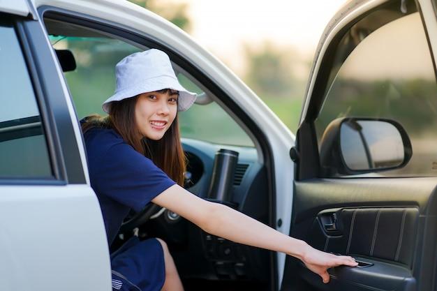 Suv車のドライバーの位置に座って、ロードトリップの前にドアを閉じる準備ができている白い帽子をかぶっている若い美しいアジアの女性。休日旅行のコンセプト
