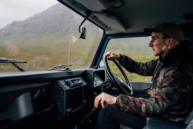 高地の古いsuvを運転している男