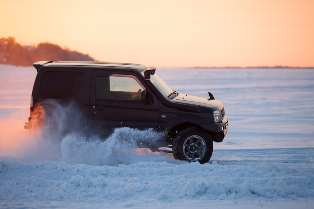 Suzuki jimny moving on ice of a frosn river at sunset