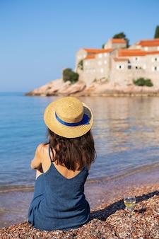 スヴェティステファン島、モンテネグロ2021年7月5日:アドリア海。セントステファン島を背景に、麦わら帽子をかぶった女の子がビーチに座っています。