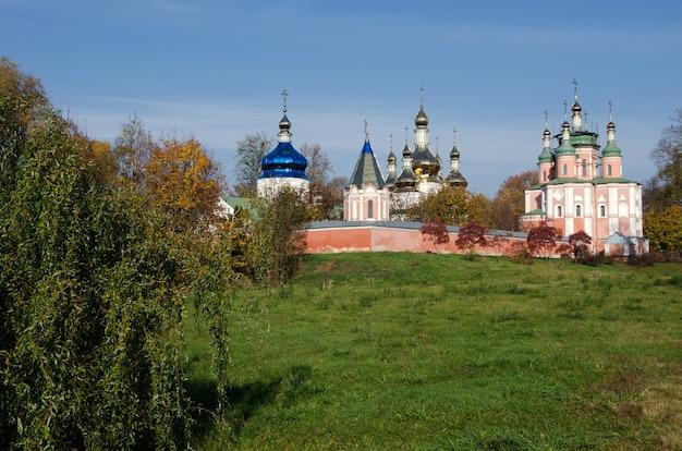 Gustynya의 가을 나무 배경에 있는 sviato-troitskyi 수도원. 체르니히프 지역. 우크라이나. 가로 야외 촬영.