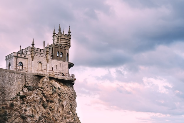 Swallow's nest castle on a rock in the black sea against the background of evening clouds, on pink tinting.