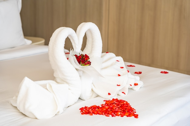 Swan towel on bed with red rose flower petals