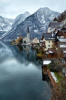 Лебеди на зимнем альпийском городе гальштат и вид на озеро хальштаттер (австрия)