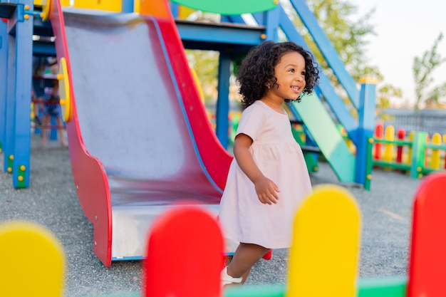 Swarthy baby with curly hair in a pale pink dress plays on street playground and rides down the hill