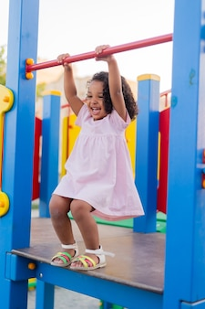 Swarthy baby with curly hair in a pale pink dress plays on a street playground