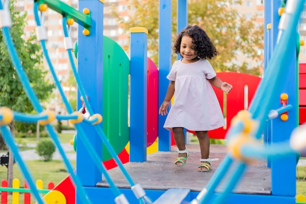 Swarthy baby with curly hair plays on a street playground the concept of a healthy lifestyle