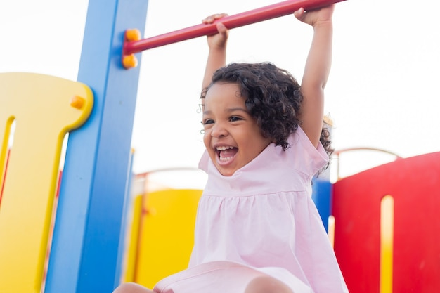 Swarthy baby with curly hair plays on a street playground girl is hanging on a horizontal bar