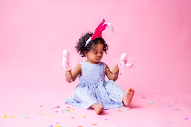 Swarthy curly baby in a blue dress and with bunny ears on her head is sitting on the floor