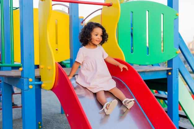 Swarty baby with curly hair in pale pink dress plays on a street playground and rides down the hill