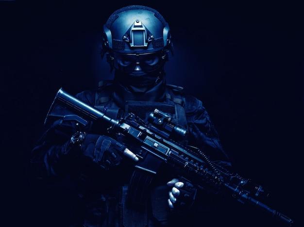Swat 전투기, 경찰 전술 그룹 구성원, 검은 제복을 입은 신속 대응 팀 사수, 방탄복, 탄도 고글 및 전투 헬멧, 광학 시력이 있는 무장 돌격 소총, 어둠 속에 서 있는