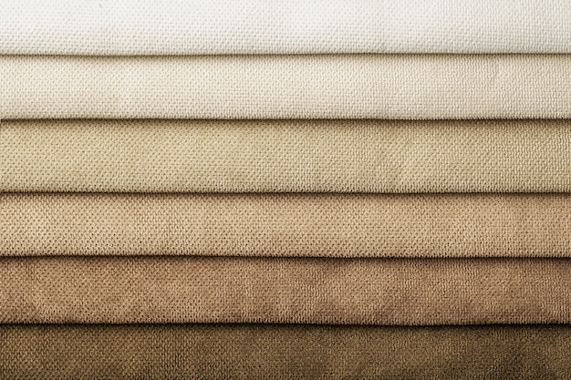 Swatch of woven textile shade and gradient of brown colors, background. catalog and palette beige tone of interior fabric for furniture, closeup. collection of cloth with wicker pattern.