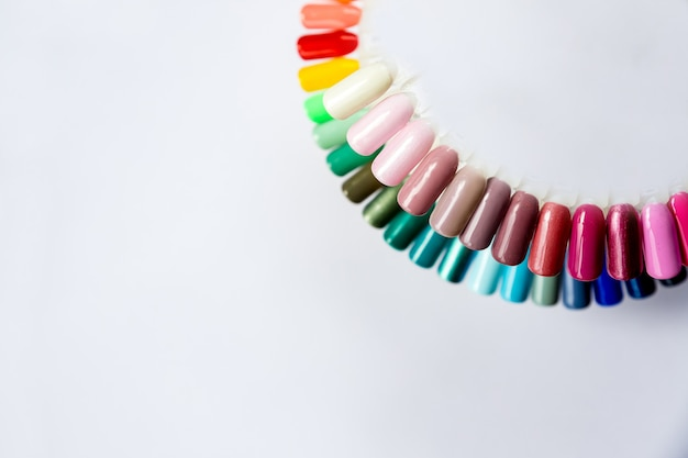 さまざまな明るい色のマニキュアサンプル。カラフルなネイルラッカーマニキュアswatches.nailアートホイールパレット。白い壁にプロのメイクアップアーティスト。