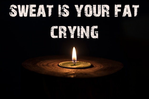 Sweat is your fat crying - white candle with dark background - in a wooden candlestick.