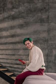 セーターとズボン。ベージュの特大のセーターと明るいズボンを着た緑髪のスタイリッシュな女性