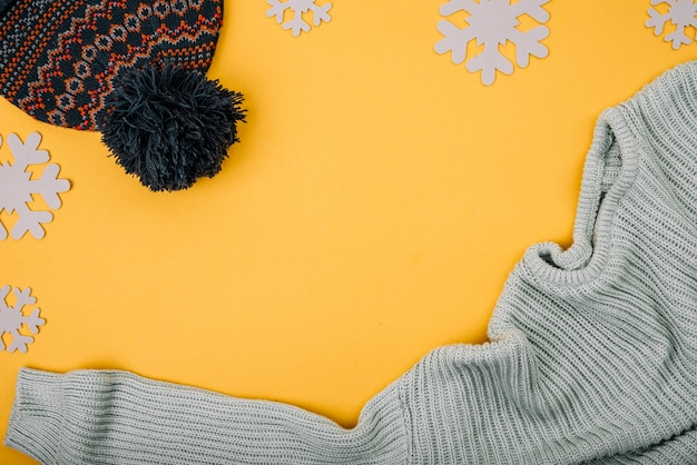 Sweater and bobble hat near snowflakes